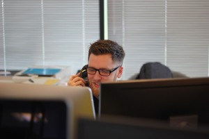 コールセンターで対応する男性の画像